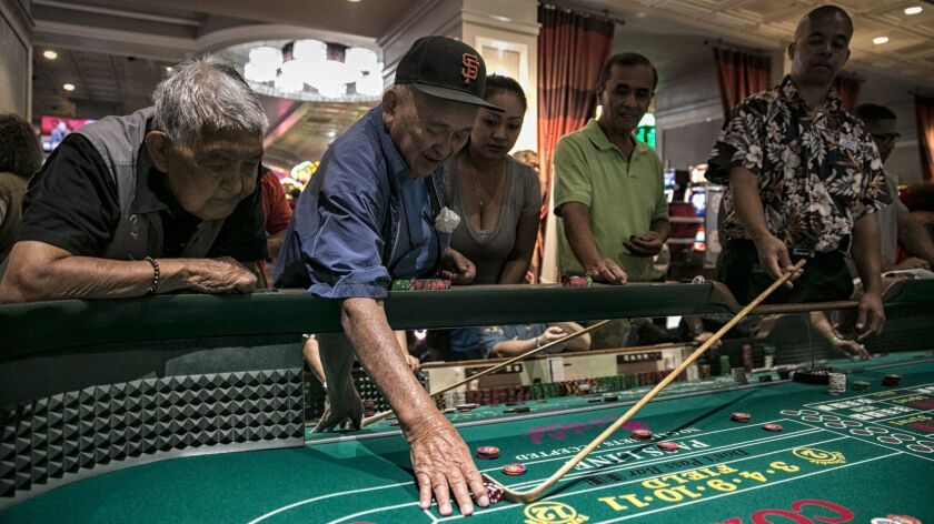 Masao Yamamoto, 82 and blind, reaches for dice during a successful series of rolls at the California
