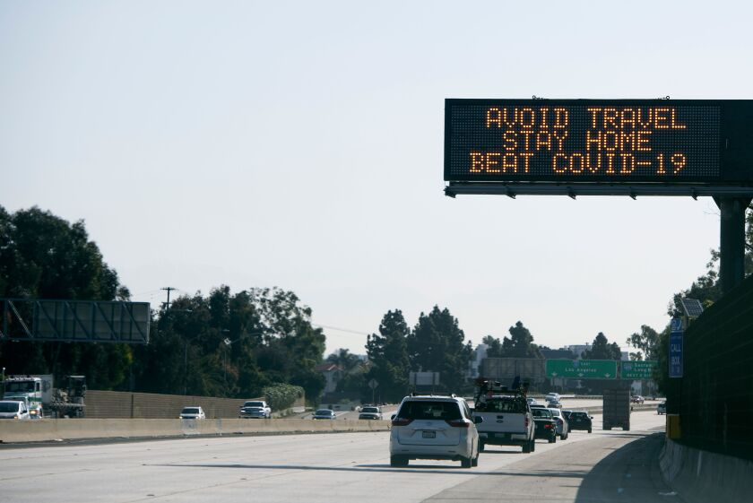"""A sign asking for drivers to """"avoid travel and stay home"""" due to the spread of coronavirus (COVID-19) is displayed over the I10 freeway on April 14, 2020, in Santa Monica, California."""