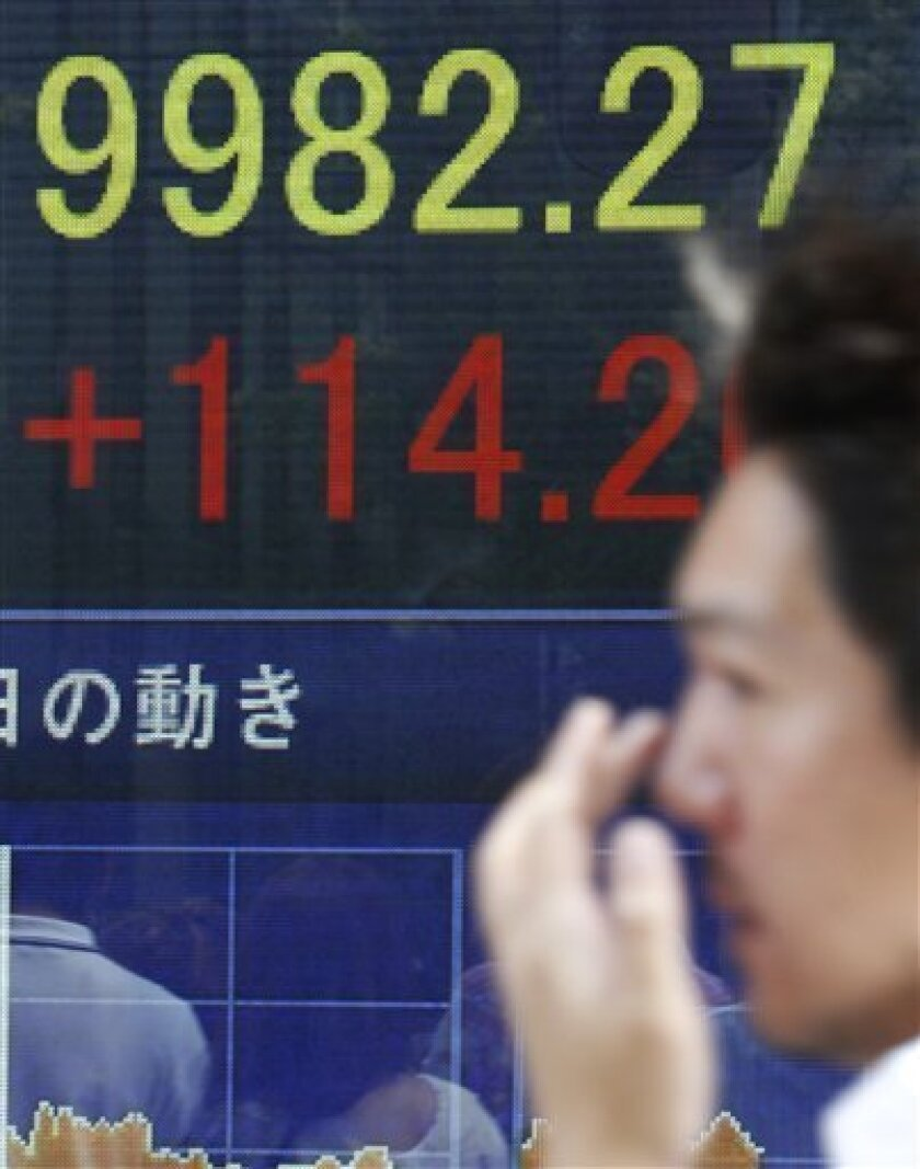 A man walks past an electronic stock indicator of Japan's Nikkei 225 index that rose to 9982.27 after gaining 114 points in Tokyo Monday, July 4, 2011. The Japanese index closed at 9,965.09, having breached the psychologically important 10,000 mark earlier in the day for the first time since May 5. Sentiment was lifted by optimism about the U.S. economy after manufacturing data for June from the Institute for Supply Management beat expectations. (AP Photo/Shizuo Kambayashi)