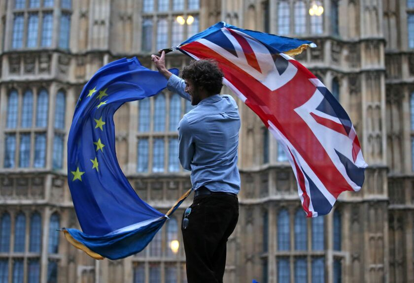 A man waves both a British flag and a European Union flag outside the Houses of Parliament in London in 2016.