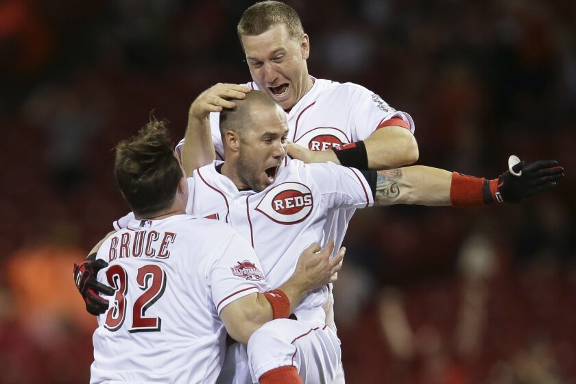 Cincinnati Reds' Skip Schumaker, center, celebrates with Jay Bruce (32) and Todd Frazier, top, after hitting a double to drive home Marlon Byrd for the game-winning run in the ninth inning of a baseball game against the Colorado Rockies, Tuesday, May 26, 2015, in Cincinnati. The Reds won 2-1. (AP P