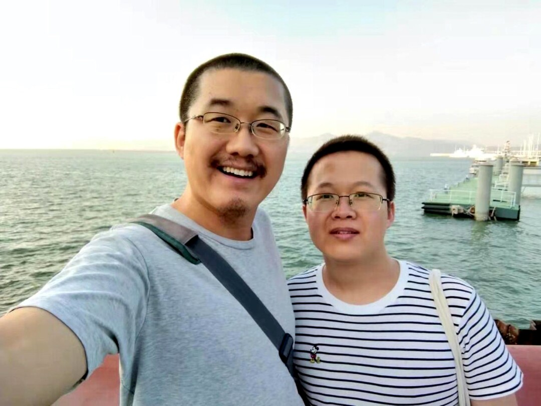 Two people in glasses pose for a photo with the ocean in the background