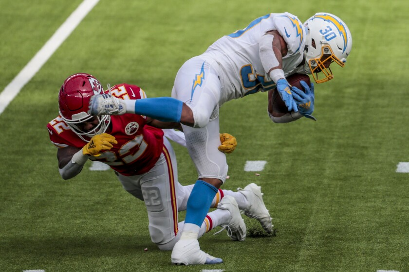 The Chargers' Austin Ekeler  slips a tackle attempt by Chiefs safety Juan Thornhill.