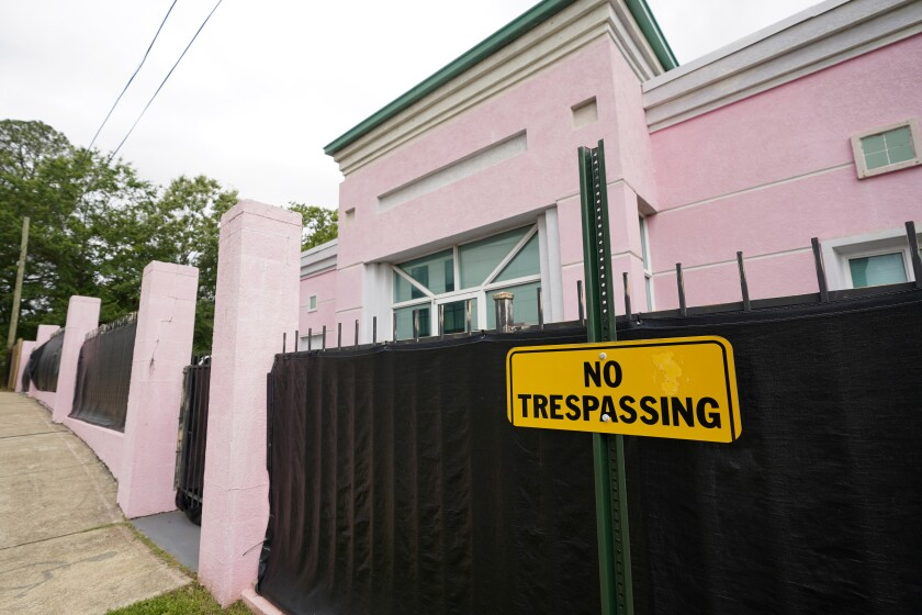 """FILE - In this May 19, 2021, file photo, the Jackson Women's Health Organization clinic, more commonly known as """"The Pink House,"""" is shrouded with a black tarp so that its clients may enter in privacy in Jackson, Miss. The Mississippi attorney general's office is expected to file briefs with the U.S. Supreme Court on Thursday to outline the state's arguments in a case that could upend nearly 50 years of court rulings on abortion rights nationwide. (AP Photo/Rogelio V. Solis, File)"""