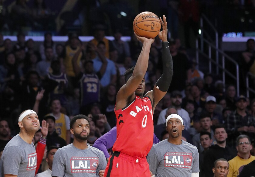 Raptors guard Terence Davis hits a three-pointer in front of the Lakers bench late in the fourth quarter at Staples Center.