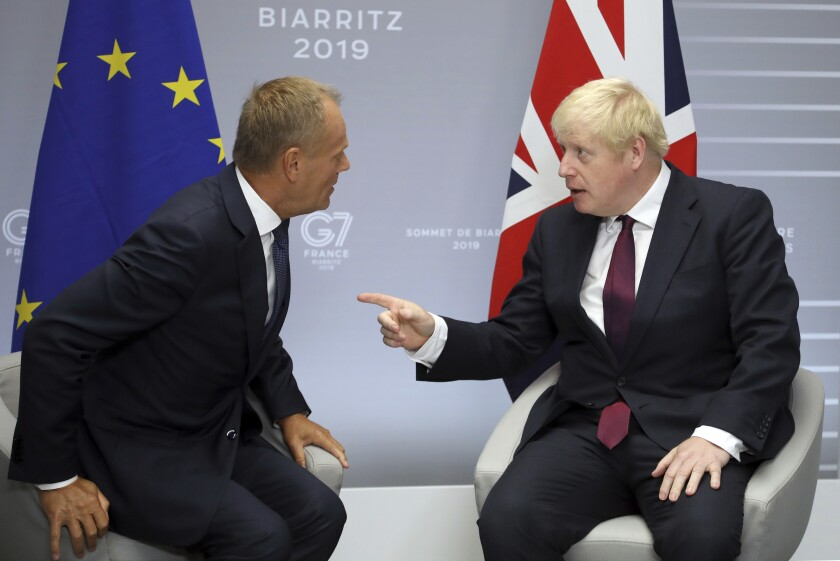 File - In this Sunday, Aug. 25, 2019 file photo, Britain's Prime Minister Boris Johnson, right, and President of the European Council Donald Tusk chat before a meeting on the side of the G-7 summit in Biarritz, France. With negotiations on the UK's departure terms from the EU hanging precariously in the balance at a time when silence seemed golden, both sides broke the spell Tuesday, Oct. 8, 2019 when Tusk directly addressed Johnson on Twitter and gave him his fill about the fast crumbling Brexit negotiations. (AP Photo/Markus Schreiber, File)
