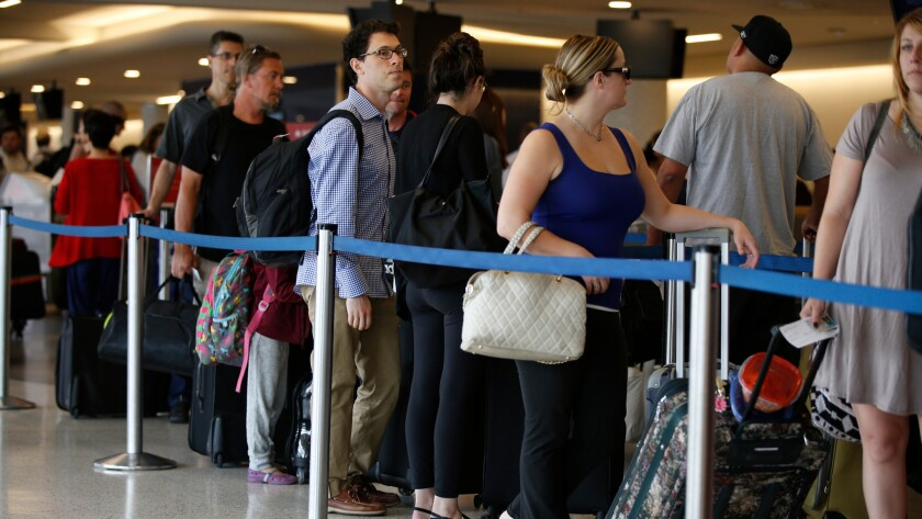 Travelers wait in long lines at the Delta Air Lines counter at LAX on the getaway day for the Labor Day holiday in September 2015. Airfares for this holiday weekend are expected to be lower than in the past few years.