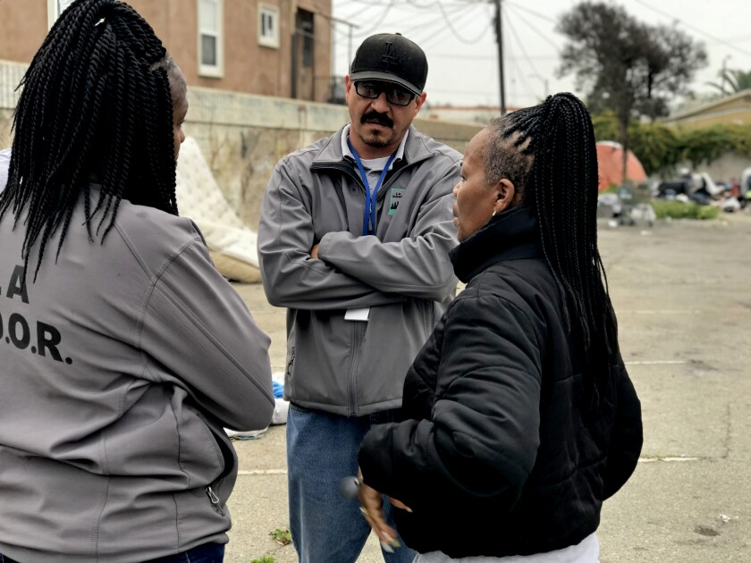 LA DOOR field team supervisor Jose Rodriguez confers with two of his outreach workers