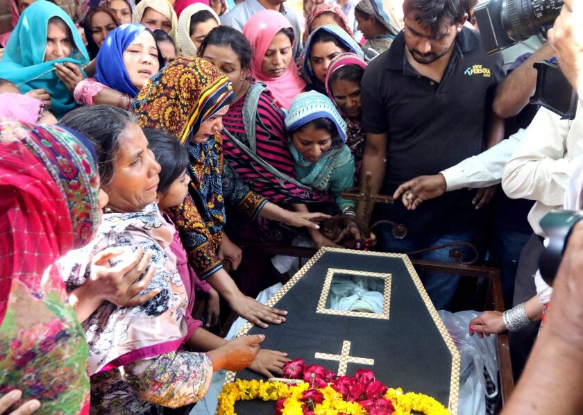 People mourn over the coffin of a victim a day after a suicide bomb attack at a park, in Lahore, Pakistan. At least 70 people, including women and children, were killed in an attack that targeted a public park in Lahore.