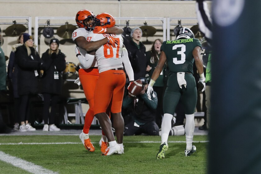 Illinois wide receiver Caleb Reams (13) hugs teammate tight end Daniel Barker (87) after Baker scored in the closing seconds to defeat Michigan State during the second half of an NCAA college football game, Saturday, Nov. 9, 2019, in East Lansing, Mich. (AP Photo/Carlos Osorio)