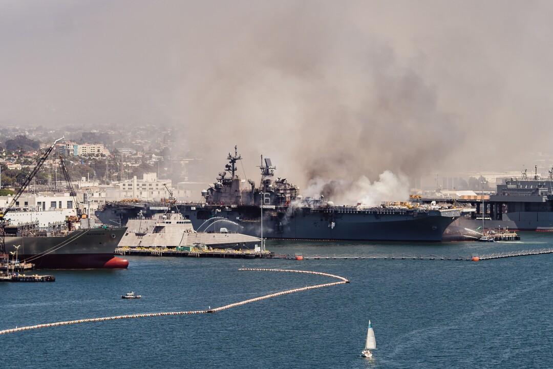 As seen from the Coronado bridge, emergency crews respond to the scene of a fire aboard the USS Bonhomme Richard.