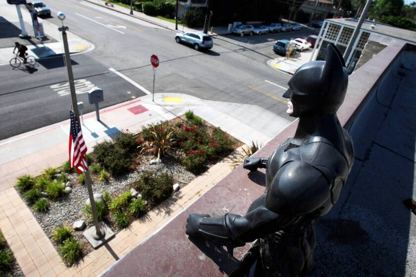 Perched atop the Belmont Heights neighborhood firehouse in Long Beach, the Batman figurine — his gaze steady, his pose vigilant — looms as a symbol of the busy nights in the neighborhood that Fire Station 4 serves.