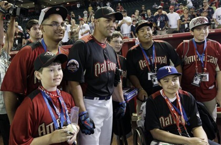 """National League's Carlos Beltran of the New York Mets poses with Make A Wish kids before the MLB All-Star baseball game Tuesday, July 12, 2011, in Phoenix. From left; Clayton """"Bo"""" Anderson, Erick Cruz, Beltran, Scott Selman, Steven Contreras and Zachary McMasters. (AP Photo/David J. Phillip)"""