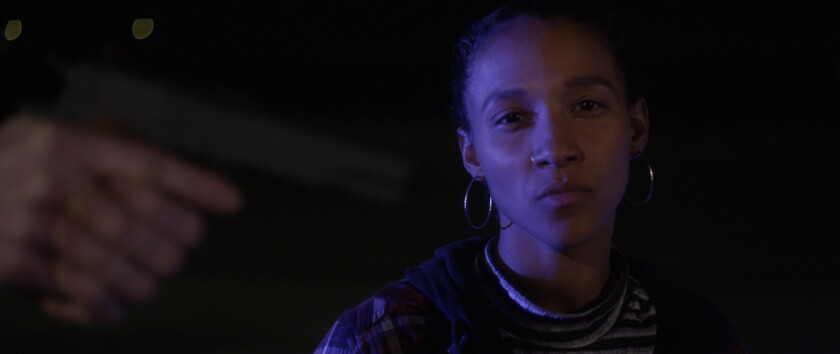 "Rhaechyl Walker in the movie ""My Name is Myeisha."" In the foreground, hands can be seen pointing a gun."