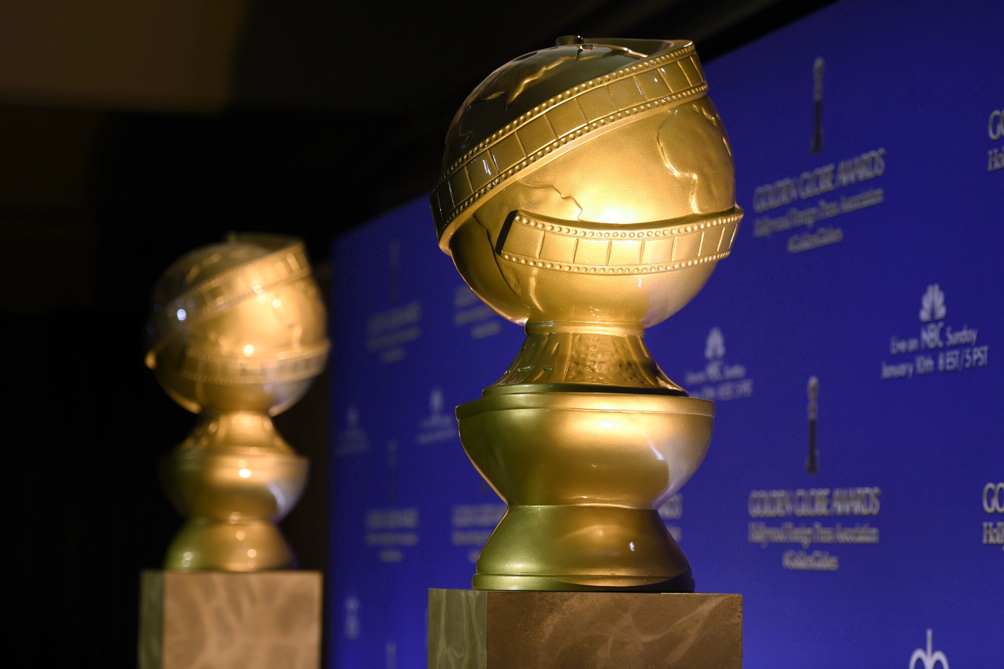 Replicas of Golden Globe statuettes against a blue backdrop