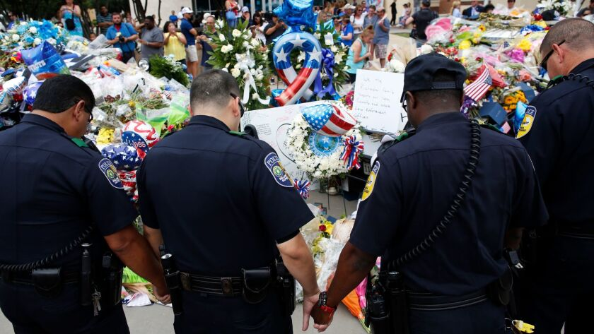 Officers pray in front of the Dallas police headquarters in July 2016 after a sniper attack that lef