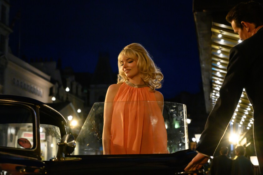 """A man opens a car door for a woman in the movie """"Last Night in Soho."""""""