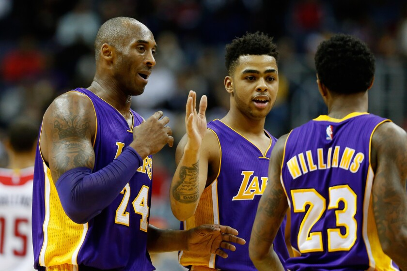 Lakers forward Kobe Bryant (24) celebrates with teammates D'Angelo Russell and Lou Williams during the second half on Wednesday.