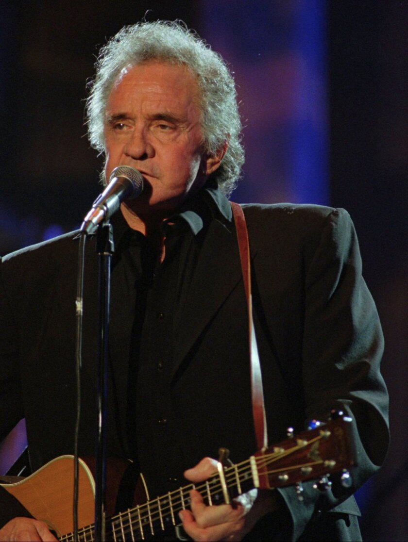 """FILE - In this Sept. 2, 1995 file photo, Johnny Cash performs during his segment of the Concert for the Rock and Roll Hall of Fame in Cleveland. The city of Folsom has completed the first section of its """"Johnny Cash Trail"""" that will pay tribute to the country music icon and his 1968 album """"At Folsom Prison."""" City officials planned to unveil the first section of the 2.5-mile trail on Saturday, Oct. 4, 2014, a pedestrian and bike bridge designed to echo Folsom State Prison's east gate guard towers (AP Photo/Mark Duncan)"""