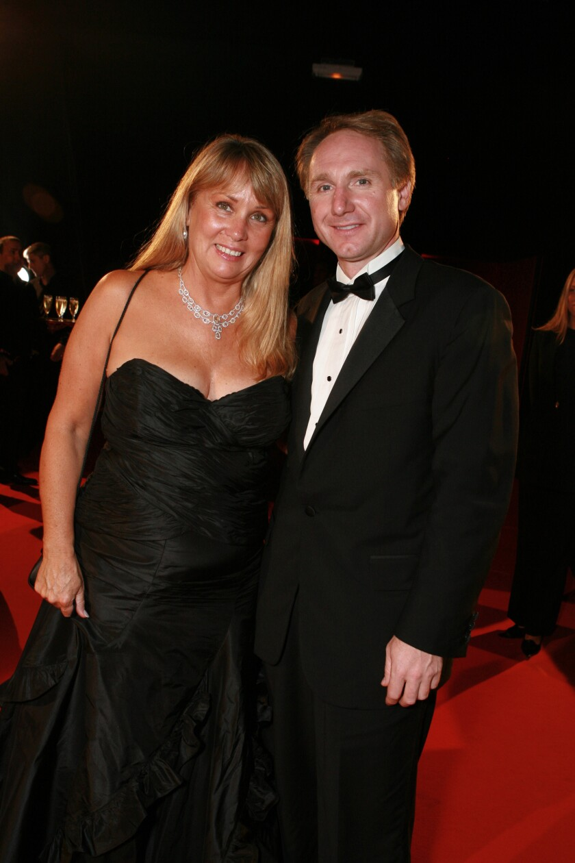 A woman in a black gown, right, and a man in a tuxedo