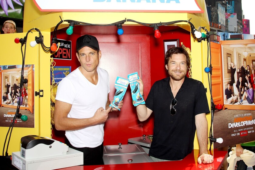 """Will Arnett, left, and Jason Bateman of """"Arrested Development"""" hold chocolate-covered frozen bananas at a replica of the Bluth's Original Frozen Banana stand in New York's Times Square."""