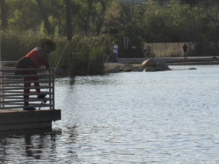 Delilah Davis of Paradise Hills waits for a bite of catfish at Santee Lakes on a recent evening.