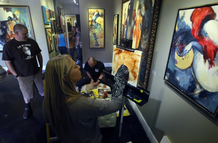 Artists Travis Sevilla, center seated, and Catherine Edlinger-Kunze, foreground, both work in acrylics Saturday during the Art-A-Thon at ArtHatch in Escondido. Paintings displayed on the walll are by Edlinger-Kunze. At left is Michael Miller, an artist stopping by to lend support to the project. Ph