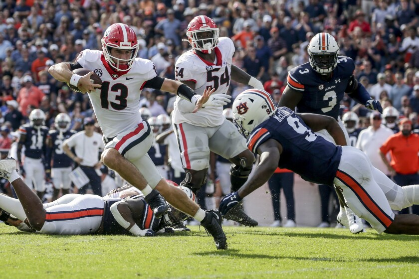 Georgia quarterback Stetson Bennett (13) carries the ball as he tries to get past Auburn linebacker Zakoby McClain (9) during the first half of an NCAA college football game Saturday, Oct. 9, 2021 in Auburn, Ala. (AP Photo/Butch Dill)
