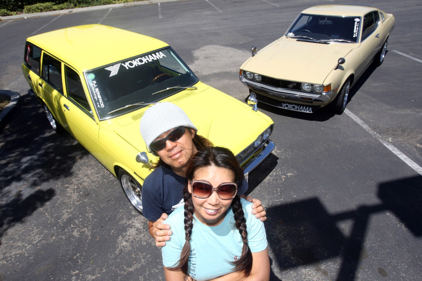 Terry, right, and Koji Yamaguchi with two of their classic cars on May 14 in La Mirada. They have a 1972 Datsun 510 wagon, left, and a 1977 Toyota Celica liftback. They are organizers of the 10th Annual Japanese Classic Car Show.