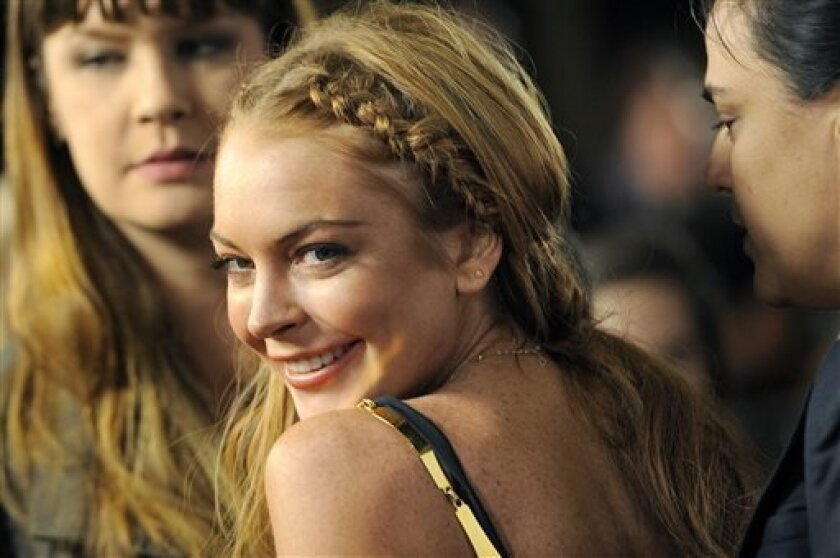 """FILE - This April 11, 2013 file photo shows actress Lindsay Lohan, a cast member in """"Scary Movie V,"""" at the premiere of the film in Los Angeles. Lohan's lawyer Mark Jay Heller told a judge at a May 2, 2013 hearing that Lohan had checked into a rehab facility per a judge's orders. (Photo by Chris Pizzello/Invision/AP, file)"""