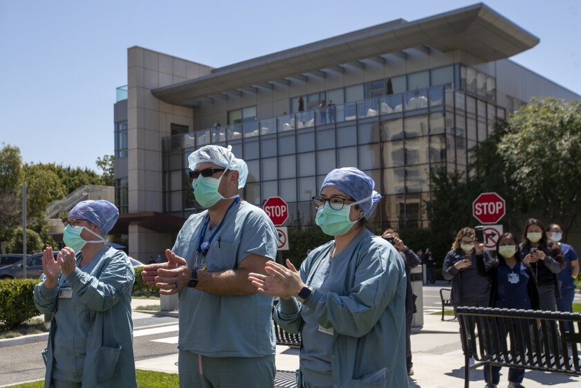 UC Irvine Medical Center healthcare workers return their gratitude as about 25 Orange County first responders' vehicles participate in a drive-by parade of thanks.