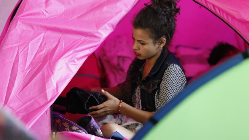 Angie, who came from Honduras with the recent migrant caravan, packs clothes in her tent at the Movimiento Juventud 2000 shelter in Zona Norte. Many from the caravan are expected to ask for asylum on Sunday.