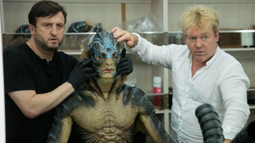 """Hill, left, and Mahan align the eye placement before gluing down the prosthetic. The creature's eyes were attached to a fiberglass """"underskull"""" so they wouldn't move when Jones made expressions."""