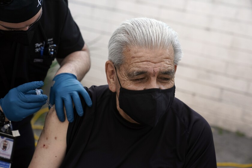 Edward Muro gets a shot of Pfizer's COVID-19 vaccine at Families Together of Orange County Community Health Center, Friday, Feb. 26, 2021, in Tustin, Calif. (AP Photo/Marcio Jose Sanchez)