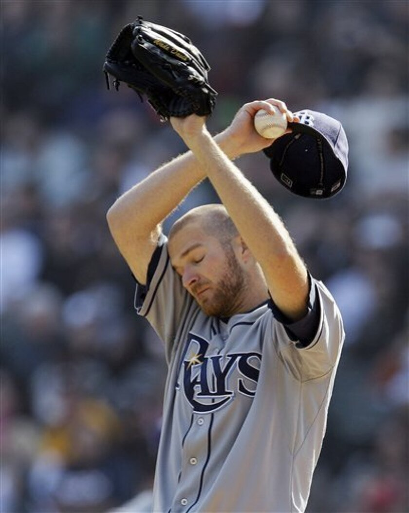 Tampa Bay Rays starting pitcher Wade Davis wipes his face after Chicago White Sox's Brent Morel doubled during the third inning of a baseball game in Chicago, Saturday, April 9, 2011. (AP Photo/Nam Y. Huh)