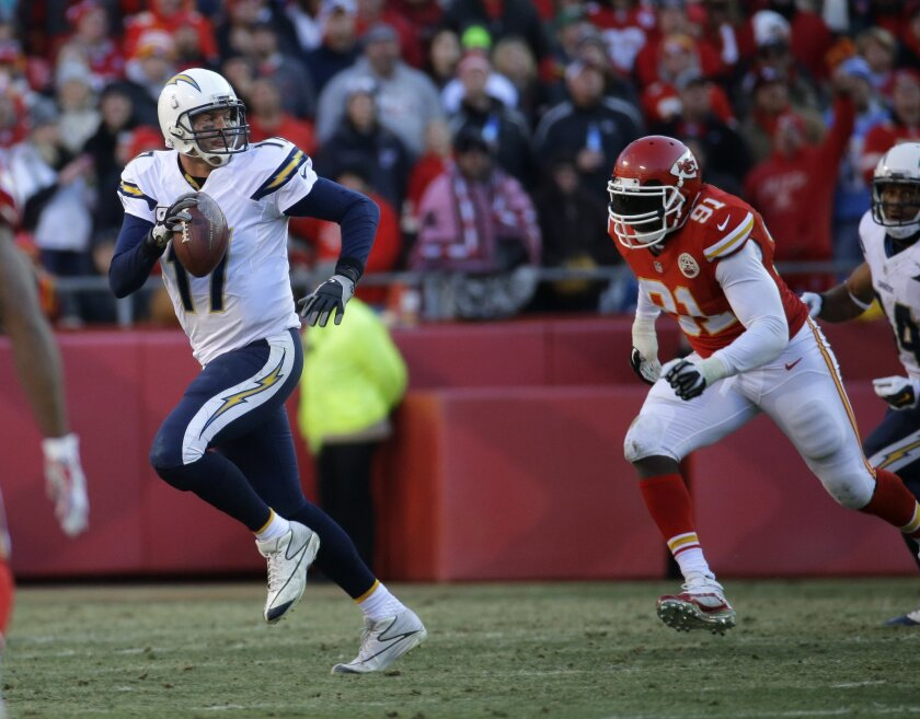 Chargers quarterback Philip Rivers is pursued by Kansas City Chiefs outside linebacker Tamba Hali (91) in the 2014 season finale. (AP Photo/Charlie Riedel)
