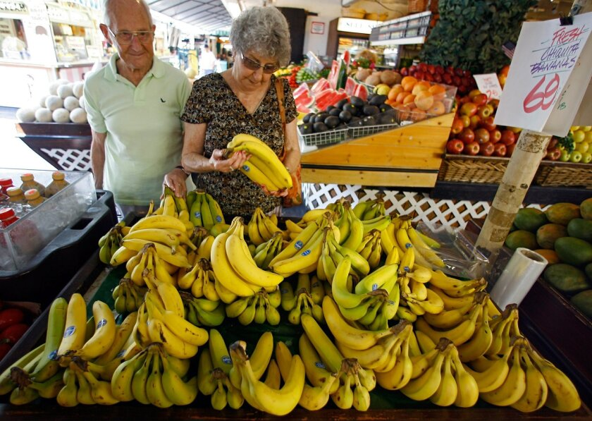 FILE - In this Aug. 15, 2007 file photo, Graham and Lola East shop for Chiquita bananas at a produce stand at the Farmers Market in Los Angeles. Not even a month after flatly rejecting a takeover bid by two Brazilian companies, Chiquita is softened its stance and will open its books to them. (AP Photo/Damian Dovarganes, File)