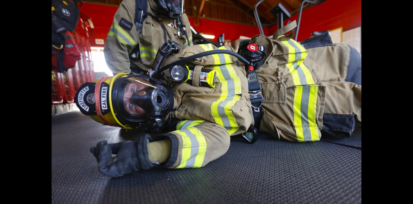 Cal Fire firefighter Trent Grinstead trains on a new style of a self-contained breathing apparatus (SCBA) which includes crawling on the ground and rolling over to simulate maneuvering through low-lying obstructions in a fire.