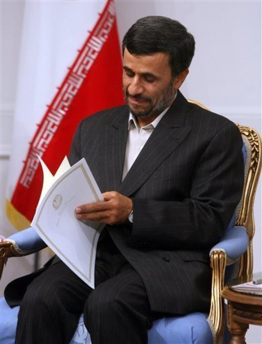 In this photo released by the semi-official Iranian Mehr News Agency, Iranian President Mahmoud Ahmadinejad, opens a letter of Venezuelan President Hugo Chavez, delivered by Venezuelan Oil Minister Rafael Ramirez, unseen, during their meeting at the presidency in Tehran, Iran, Wednesday, July 1, 2009. (AP Photo/Mehr News Agency,Sajjad Safari) EDITORS NOTE AS A RESULT OF AN OFFICIAL IRANIAN GOVERNMENT BAN ON FOREIGN MEDIA COVERING SOME EVENTS IN IRAN, THE AP WAS PREVENTED FROM INDEPENDENT ACCESS TO THIS EVENT