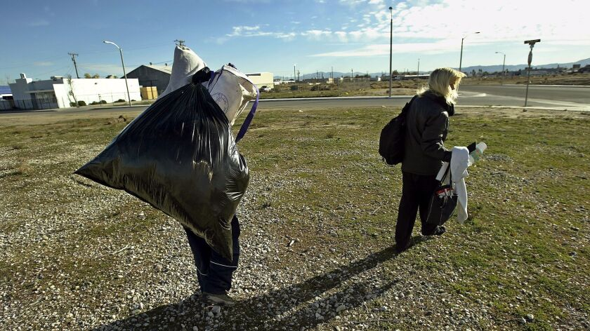 Rachael Hannon and a friend, who asked not to be identified, walk in front of an Antelope Valley shelter which had no room for them to stay on Nov. 30, 2004.