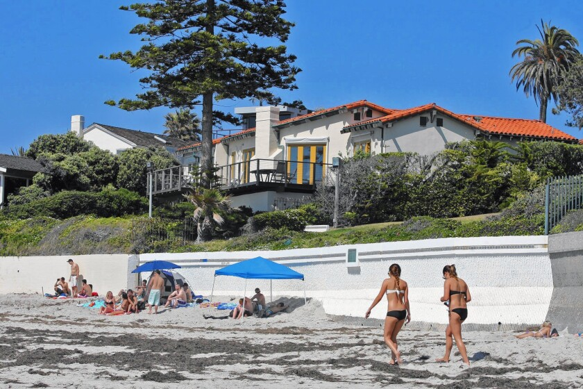People visit the beach in front of Mitt Romney's La Jolla home, which sold recently for $23.5 million.