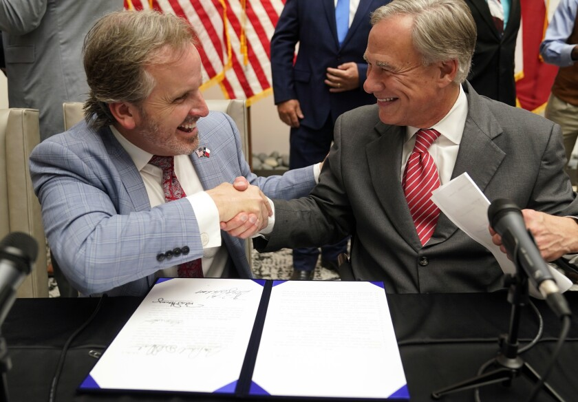 Texas Gov Greg Abbott and State Sen. Bryan Hughes, R-Mineola, shake hands after Abbott signed Senate Bill 1, also known as the election integrity bill, into law in Tyler, Texas, Tuesday, Sept. 7, 2021. The sweeping bill signed Tuesday by the two-term Republican governor further tightens Texas' strict voting laws. (AP Photo/LM Otero)