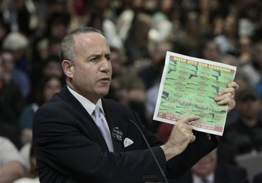 State Senate President Pro Tem Darrell Steinberg, D-Sacramento, displays a newspaper ad showing the type of assault style rifle that his proposed legislation would ban in California during a hearing of the Senate Public Safety Committee in Sacramento, Calif., Tuesday, April 16, 2013.  Steinberg's