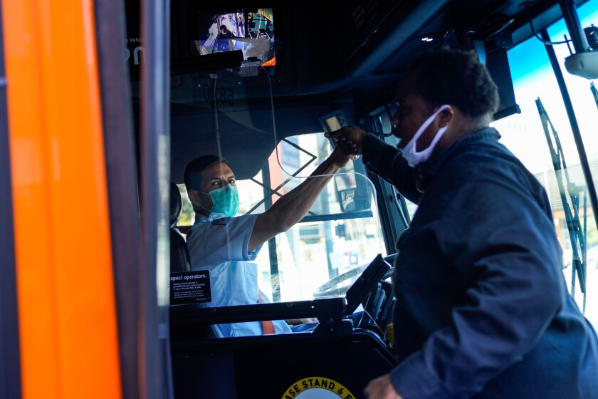 Bus operator Jimi Pollard, right, greets a fellow operator who stopped his bus at the stoplight in downtown L.A. on Friday.
