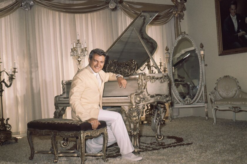 Entertainer Liberace  is seated at his piano in his Beverly Hills home in California on June 17, 1961.    Liberace's home is reported to have 28 rooms.