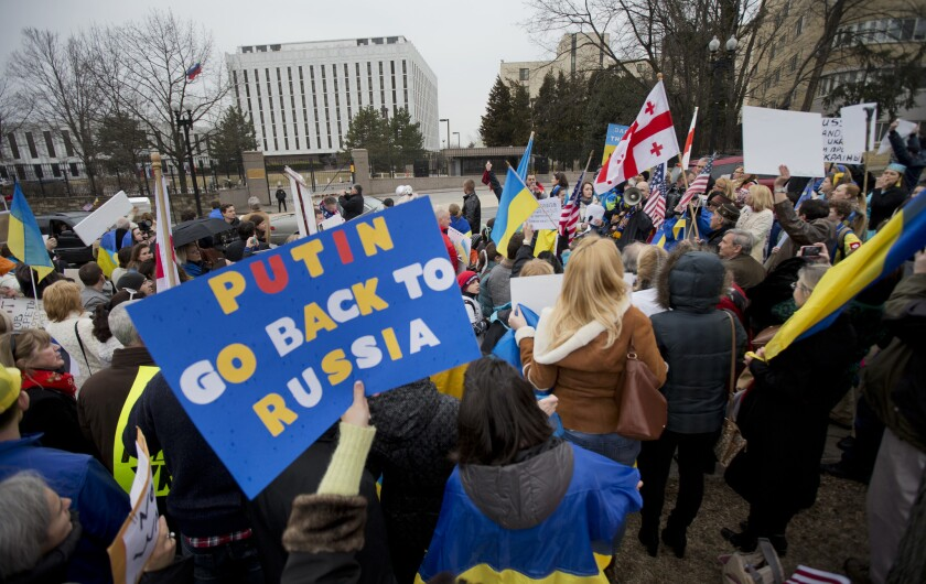"""Demonstrators are seen at a protest rally in front of the Russian embassy in Washington. Igniting a tense standoff, Russian forces surrounded a Ukrainian army base Sunday just as Ukraine began mobilizing in response to the surprise Russian takeover of Crimea. Outrage over Russia's tactics mounted in world capitals, with U.S. Secretary of State John Kerry calling on President Vladimir Putin to pull back from """"an incredible act of aggression."""""""