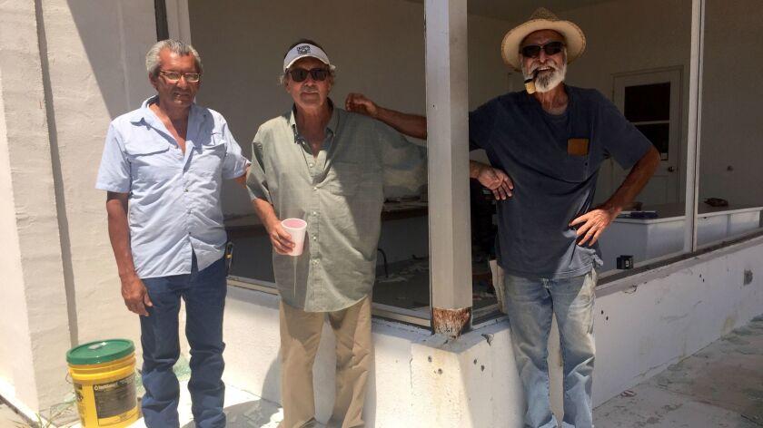 Richard Gonzalez, C.J. Duckworth and Michael Gian near the broken windows of Duckworth's sign shop i