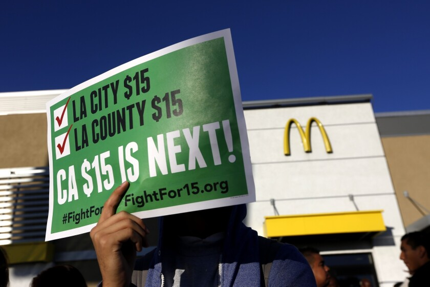 A person holds up a sign pushing for a $15 minimum wage in California.