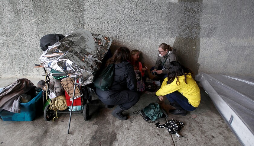 Homeless-outreach workers talk to a woman named Sandy as she seeks shelter from the rain beneath the 405 Freeway in Venice earlier this year.