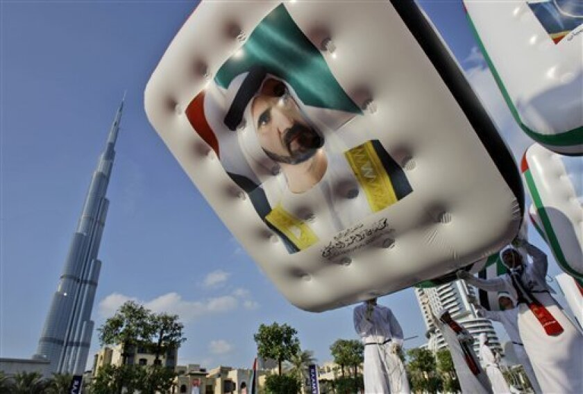 An Emarati man tries to control a balloon with the image of Dubai's ruler and UAE prime minister Sheik Mohammed bin Rashid Al Maktoum during the UAE national day parade in Dubai, United Arab Emirates, Tuesday, Dec. 1, 2009. Talking to the media Tuesday, Sheik Mohammed said, Dubai's economy is 'strong' and 'solid' and the world does not understand what is happening in Dubai, in his first public comments since the financial meltdown in the former Arab boomtown. (AP Photo/Kamran Jebreili)